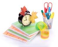 Pile of writing-book and alarm clock Stock Photos