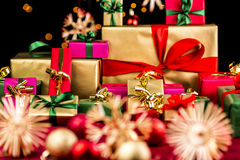 Pile of Xmas Presents in Plain Colors. Heap of Christmas gifts in mainly golden and red colors. Blurred baubles and stars on red blanket in front. Bokeh effect Stock Photos