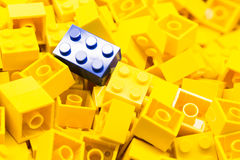 Pile of  yellow color building blocks with selective focus and highlight on one particular blue block using available light Stock Photo