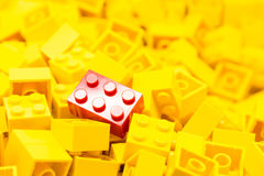 Pile of yellow color building blocks with selective focus and highlight on one particular red block using available light.  stock image