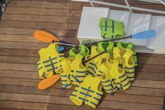 A pile of yellow and green life vests with boat paddles piled on a wooden dock and some white plastic stairs stock images