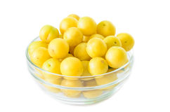 Pile of yellow mirabelle plums in bowl isolated on white background Stock Photo