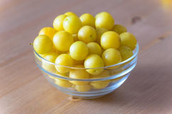 Pile of yellow mirabelle plums in bowl on wooden table Royalty Free Stock Photography