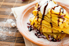 Pile of yellow pancakes with sour cream and sprinkled with choco Stock Image
