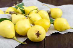 A pile of yellow pears scattered on a dark wooden table. Royalty Free Stock Images