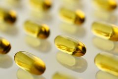 Pile of yellow transparent omega-3 pills arranged in diagonal line. On white table closeup. Life save lab food additives prescribe cod liver and salmon soft gel stock photos
