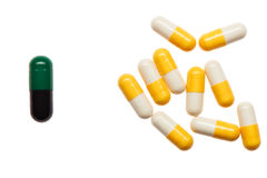 Pile of yellow and white capsules and one bigger green and black capsule Stock Image