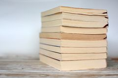 Pile of yellowed old used paperback books on wood desk and light blue background stock photography