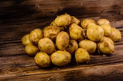 Pile of the young potato on wooden table. Pile of young potato on rustic wooden table Stock Image