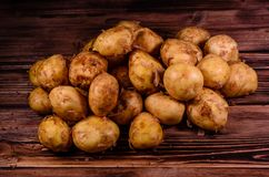 Pile of the young potato on wooden table. Top view. Pile of young potato on rustic wooden table. Top view Royalty Free Stock Photography
