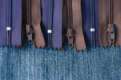 Pile of zippers on denim material Royalty Free Stock Images