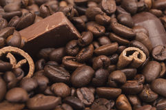 Piled coffee beans, cinnamon sticks and chocolate. Close up of piled coffee beans, cinnamon sticks and chocolate Royalty Free Stock Images