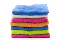Piled colorful towels isolated on white Stock Photos