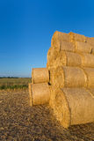 Piled hay bales on a field against blue sky Royalty Free Stock Image