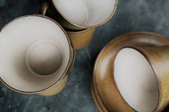 Piled old stone mugs, vintage or retro color. Piled old stone mugs, vintage or retro, on a grey stone surface Stock Images