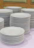 Piled up of white plates on table Stock Photos