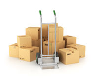Piles of cardboard boxes with hand truck Royalty Free Stock Photos