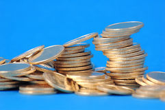 Piles of coins. On blue background Royalty Free Stock Photos