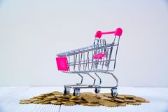 Piles of coins and shopping cart or supermarket trolley on white. Wood working table, business and financial concept idea Stock Photography
