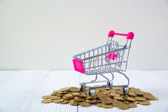 Piles of coins and shopping cart or supermarket trolley on white. Wood working table, business and financial concept idea Stock Photo