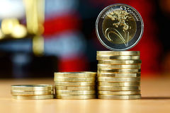 Piles of coins on a table. Piles of euro coins on a table on sand clock background stock photo