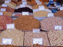 Piles of colorful nuts and spices at a food market stock image