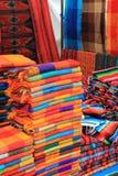 Colorful fabric for sale at a Mexican craft market. Piles of colorful woven fabrics for sale at a craft market in San Cristobal de las Casas, Chiapas, Mexico Stock Image