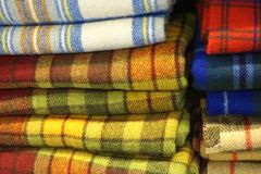 Piles of colorful woven wool tartan plaid cloth fabric. Worn by clan members in Scotland and elsewhere Royalty Free Stock Photography