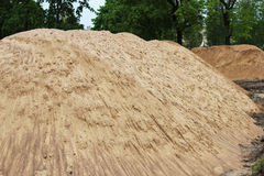 A piles of construction sand on the site for the construction of the city stadium. Royalty Free Stock Images