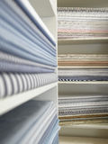 Piles of cotton fabric on shelfs Stock Photos