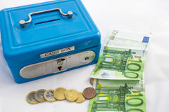 Piles d'euro pièces de monnaie et billets de banque dans une boîte d'argent liquide Image stock