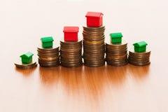 Piles de la maison de pièces de monnaie, verte et rouge Image libre de droits