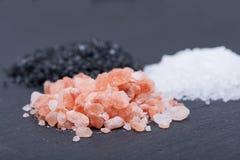 Piles de Lava Sea Salt noir hawaïen, de sel brut de mer blanche et de sel rose de l'Himalaya sur l'obscurité photographie stock libre de droits