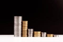 Piles de pièces de monnaie au-dessus de fond noir Photo libre de droits