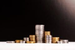 Piles de pièces de monnaie au-dessus de fond noir Images stock