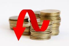 Piles de pièces de monnaie avec une flèche rouge vers le bas Images stock