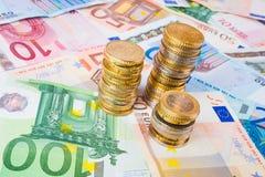 Piles de pièces de monnaie sur des billets de banque Photo libre de droits