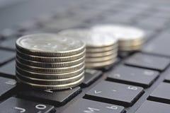 Piles de pièces de monnaie sur le clavier d'ordinateur portable Photographie stock