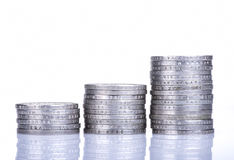 Piles de pièces de monnaie sur le fond blanc Photos stock