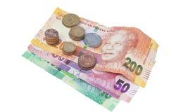 Piles de pièces de monnaie sur trois billets de banque sud-africains Photos stock