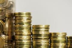 Piles de pièces de monnaie à côté d'un pot complètement de pièces de monnaie image stock