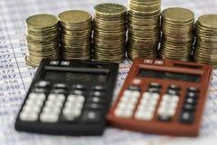 Piles de pièces de monnaie avec les calculatrices rouges et noires dans l'avant photographie stock