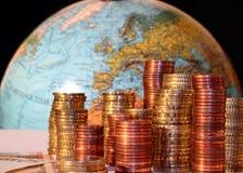 Piles de pièces de monnaie d'euro et de cent devant l'Europe Photographie stock