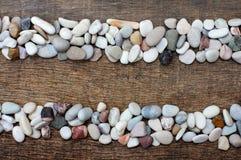 Piles de pierres colorées sur la texture en bois Image libre de droits