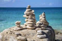 Piles de pierres dans l'équilibre à une plage Photographie stock