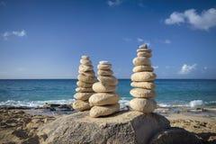 Piles de pierres dans l'équilibre à une plage Photographie stock libre de droits