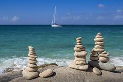 Piles de pierres dans l'équilibre à une plage avec le yacht sur le fond Photo libre de droits