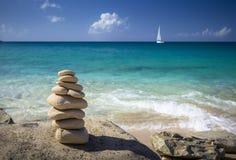 Piles de pierres dans l'équilibre à une plage avec le yacht sur le fond Image libre de droits