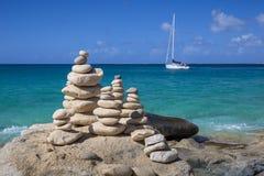 Piles de pierres dans l'équilibre à une plage avec le yacht sur le fond Photos libres de droits