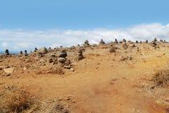 Piles de pierres sur le désert de sable Photographie stock libre de droits